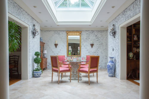 white painted brick atrium with bold coral red chairs
