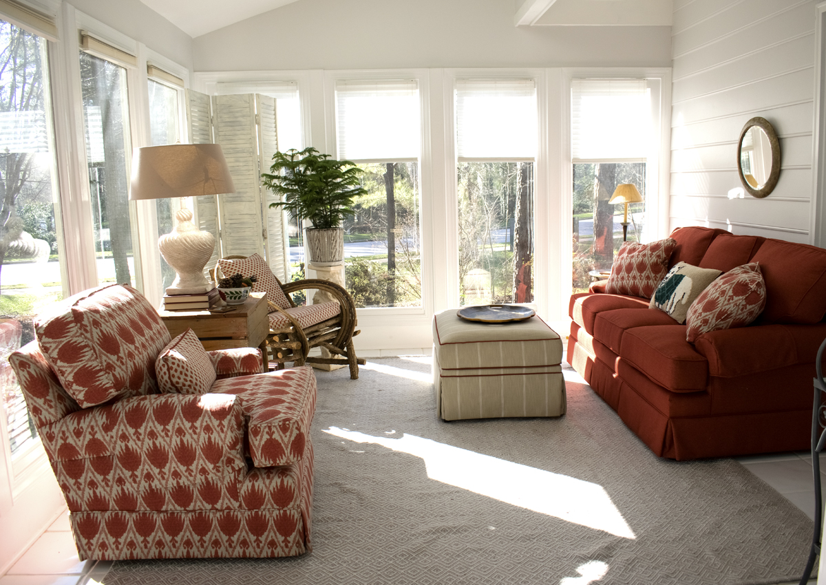Sun Room Rust Couch Striped Ottoman Sunlit Windows