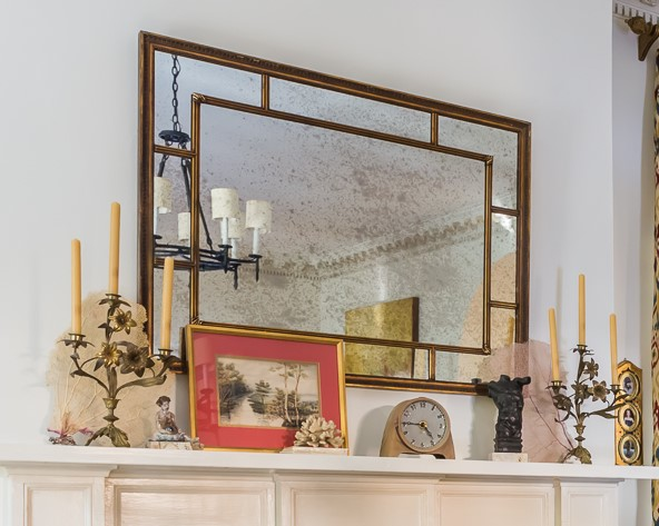 artwork and collectibles reflected in mirror over mantel